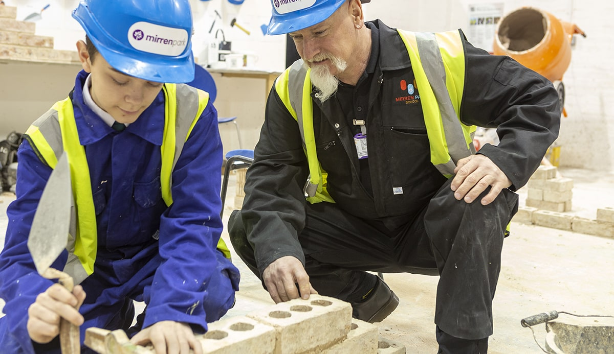 Student being instructed in brick laying