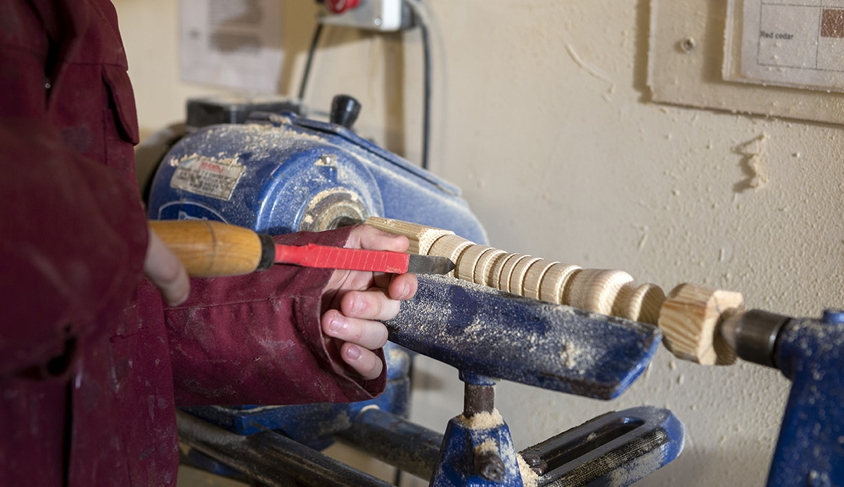 Student being instructed on the use of a woodworking lathe